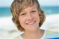 Portrait of a boy smiling on the beach Stock Photo - Premium Royalty-Freenull, Code: 6108-06905227