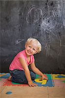Smiling girl playing with number puzzle in front of a blackboard Stock Photo - Premium Royalty-Freenull, Code: 6108-06905309