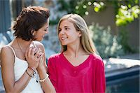 Close-up of a woman and her daughter smiling together Stock Photo - Premium Royalty-Freenull, Code: 6108-06905597