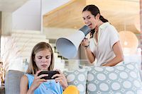 Woman shouting through a megaphone at his daughter for playing video game Stock Photo - Premium Royalty-Freenull, Code: 6108-06905612