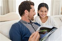 Man and his daughter reading a magazine Stock Photo - Premium Royalty-Freenull, Code: 6108-06905623