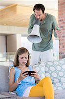 Man shouting into a megaphone at his daughter for playing video game Stock Photo - Premium Royalty-Freenull, Code: 6108-06905627