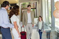 Man with his daughter arriving at his friends home from holiday Stock Photo - Premium Royalty-Freenull, Code: 6108-06905750