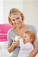 Woman feeding milk her baby with a bottle Stock Photo - Premium Royalty-Freenull, Code: 6108-06906041
