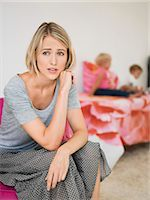 sad child sitting - Woman looking worried with her children in the background Stock Photo - Premium Royalty-Freenull, Code: 6108-06906052