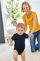 Smiling mother helping her baby to walk Stock Photo - Premium Royalty-Freenull, Code: 6108-06906098