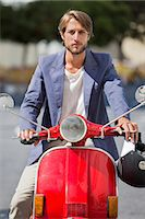 Man riding a scooter Stock Photo - Premium Royalty-Freenull, Code: 6108-06906535