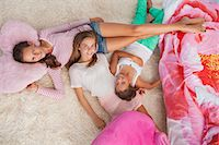Three girls lying on a carpet at a slumber party Stock Photo - Premium Royalty-Freenull, Code: 6108-06907010
