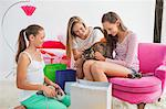 Girls playing with cat at a slumber party Stock Photo - Premium Royalty-Freenull, Code: 6108-06907037