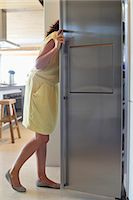 fridge - Woman looking into a refrigerator in the kitchen Stock Photo - Premium Royalty-Freenull, Code: 6108-06907094