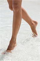 female feet close up - Woman walking in water on the beach Stock Photo - Premium Royalty-Freenull, Code: 6108-06907283