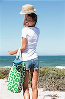 Happy woman carrying a bag on the beach Stock Photo - Premium Royalty-Freenull, Code: 6108-06907291