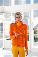 Portrait of a woman tossing an orange Stock Photo - Premium Royalty-Freenull, Code: 6108-06907414