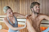 Woman massaging on her friend's back with a massager in a sauna Stock Photo - Premium Royalty-Freenull, Code: 6108-06907532