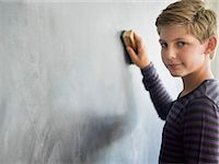 Boy cleaning blackboard with a duster in a classroom Stock Photo - Premium Royalty-Freenull, Code: 6108-06907666