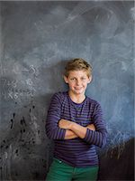 Boy smiling with his arms crossed in front of a blackboard in a classroom Stock Photo - Premium Royalty-Freenull, Code: 6108-06907701