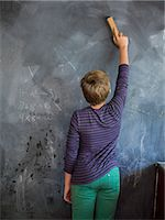 Boy cleaning blackboard with a duster in a classroom Stock Photo - Premium Royalty-Freenull, Code: 6108-06907709