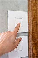 Close-up of a person's hand pressing a light switch Stock Photo - Premium Royalty-Freenull, Code: 6108-06907831