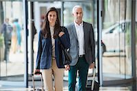 Business couple pulling suitcases in a hotel lobby Stock Photo - Premium Royalty-Freenull, Code: 6108-06907851