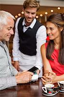 person on phone with credit card - Waiter showing credit card reader to a couple on a table in a restaurant Stock Photo - Premium Royalty-Freenull, Code: 6108-06907863