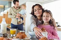 Girl having breakfast beside her mother at a kitchen counter Stock Photo - Premium Royalty-Freenull, Code: 6108-06908084