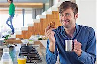 stove - Man having breakfast at a kitchen counter with his wife in the background Stock Photo - Premium Royalty-Freenull, Code: 6108-06908086