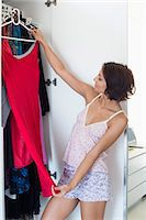 Woman choosing clothes from wardrobe Stock Photo - Premium Royalty-Freenull, Code: 6108-06908089