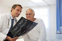 Doctor and patient examining x-rays in hospital room Stock Photo - Premium Royalty-Freenull, Code: 6113-06908210