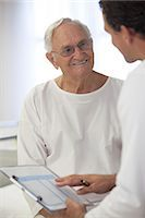 Doctor talking with older patient in hospital room Stock Photo - Premium Royalty-Freenull, Code: 6113-06908259