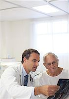Doctor showing x-rays to older patient in hospital room Stock Photo - Premium Royalty-Freenull, Code: 6113-06908307