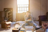 Woman unpacking boxes in attic Stock Photo - Premium Royalty-Freenull, Code: 6113-06908567