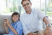 rich lifestyle - Father and son with change jar on sofa Stock Photo - Premium Royalty-Freenull, Code: 6113-06908708