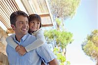 Father carrying daughter piggy back outdoors Stock Photo - Premium Royalty-Freenull, Code: 6113-06908801
