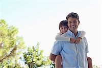 Father carrying daughter piggy back outdoors Stock Photo - Premium Royalty-Freenull, Code: 6113-06908804