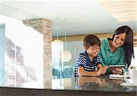 preteen touch - Mother and son using tablet computer in kitchen Stock Photo - Premium Royalty-Freenull, Code: 6113-06908835