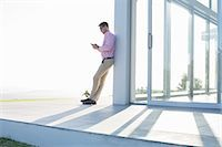 Businessman using cell phone outside office Stock Photo - Premium Royalty-Freenull, Code: 6113-06908959