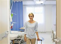 Patient wheeling luggage out of hospital room Stock Photo - Premium Royalty-Freenull, Code: 6113-06909068