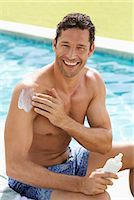 prevention - Man applying sunscreen by swimming pool Stock Photo - Premium Royalty-Freenull, Code: 6113-06909317