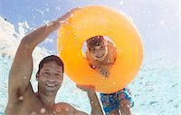 Father and son playing in swimming pool Stock Photo - Premium Royalty-Freenull, Code: 6113-06909318