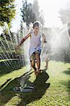 Boy playing in sprinkler in backyard Stock Photo - Premium Royalty-Freenull, Code: 6113-06909325