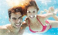 people and vacation - Couple swimming in pool Stock Photo - Premium Royalty-Freenull, Code: 6113-06909333