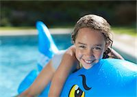 Girl riding inflatable toy in swimming pool Stock Photo - Premium Royalty-Freenull, Code: 6113-06909334