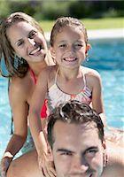 Family smiling in swimming pool Stock Photo - Premium Royalty-Freenull, Code: 6113-06909346