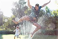 Father and son playing in sprinkler in backyard Stock Photo - Premium Royalty-Freenull, Code: 6113-06909353