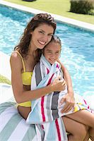 Mother and daughter relaxing by swimming pool Stock Photo - Premium Royalty-Freenull, Code: 6113-06909372