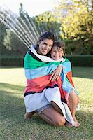 Mother and son wrapped in towel in backyard Stock Photo - Premium Royalty-Freenull, Code: 6113-06909394