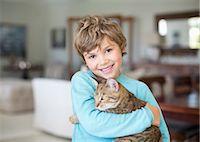 Boy hugging cat in living room Stock Photo - Premium Royalty-Freenull, Code: 6113-06909400