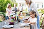 Family setting table outdoors