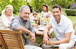 Family smiling together at table Stock Photo - Premium Royalty-Free, Artist: Blend Images, Code: 6113-06909435