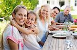 Mother and daughter hugging at table outdoors